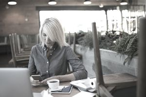 Female cafe business owner texting with cell phone at laptop