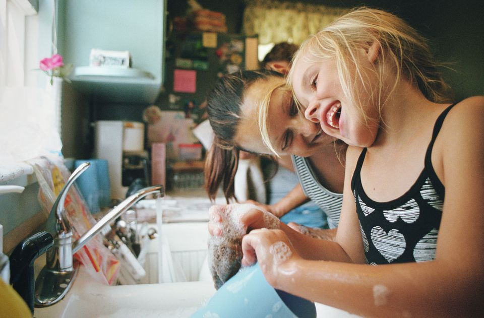 Laughing girl washing dishes with grandmother