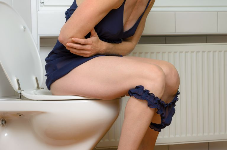 Midsection Of Woman Sitting In Bathroom