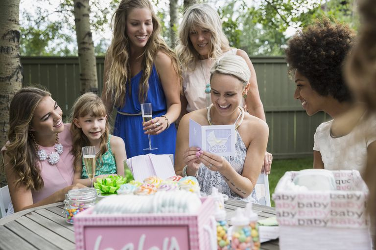 Pregnant woman reading card at backyard baby shower