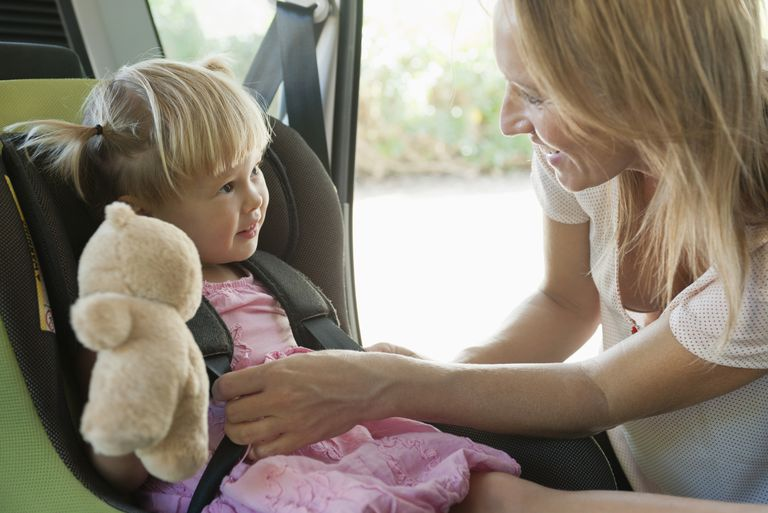 mother fastening daughter into car seat