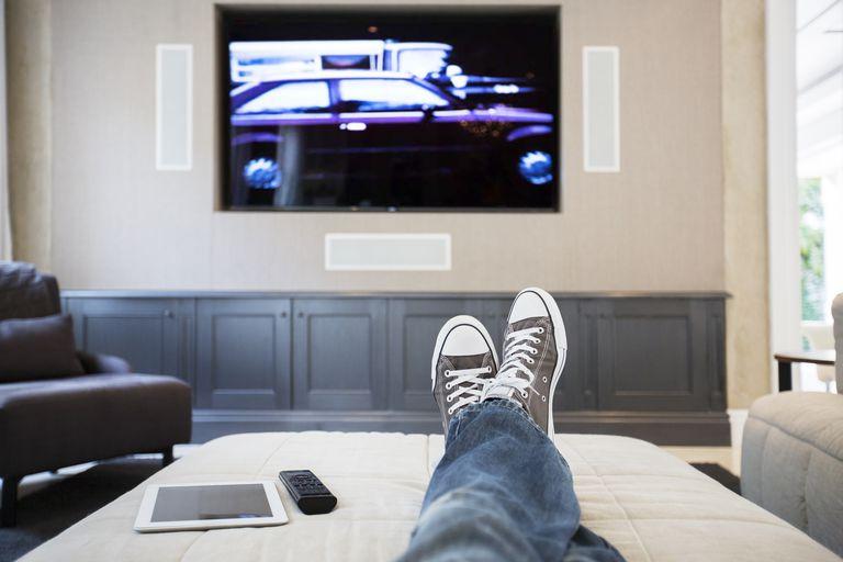 Womans feet on ottoman watching TV