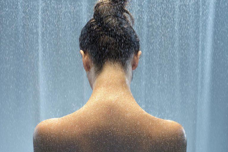 Woman taking shower, rear view
