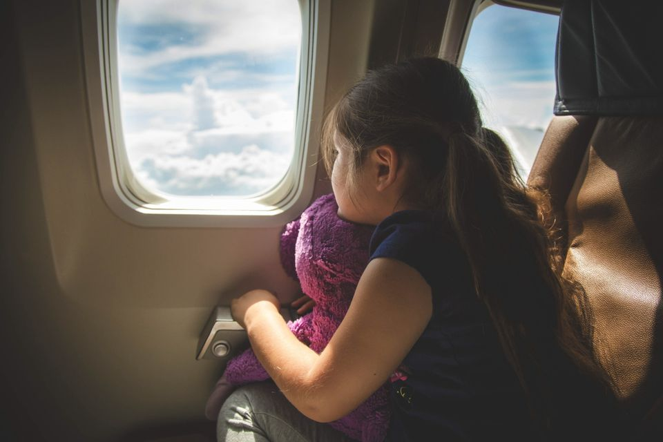 Young girl looking out of a plane window.