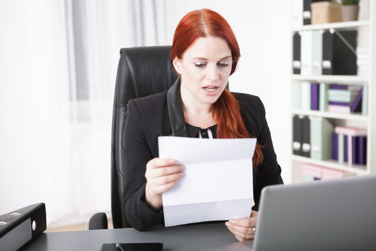 Unemployed woman reading COBRA letter in her home office.