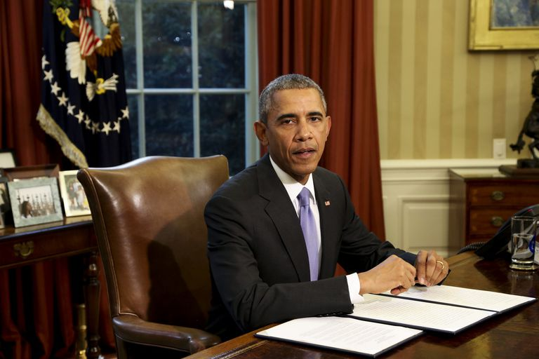 President Obama sitting at his desk vetoing a bill