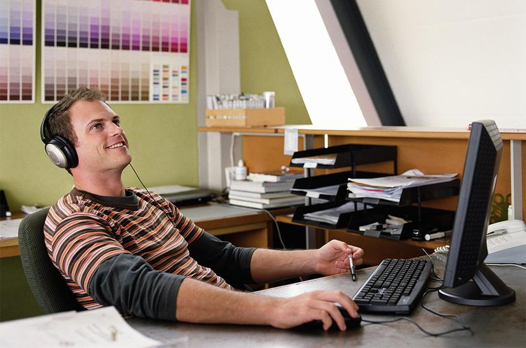 Man wearing headphones sitting at computer, smiling