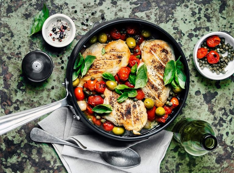 Chicken in a frying pan with tomatoes, spinach leaves, and olives