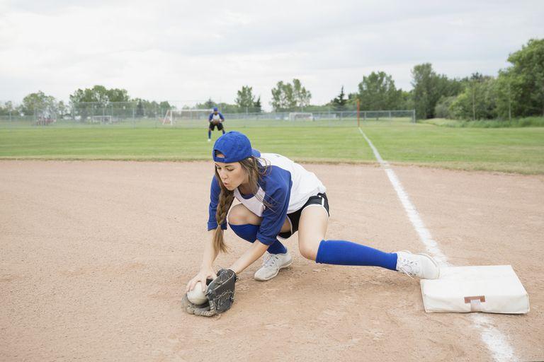 Baseball player scooping up ball at base