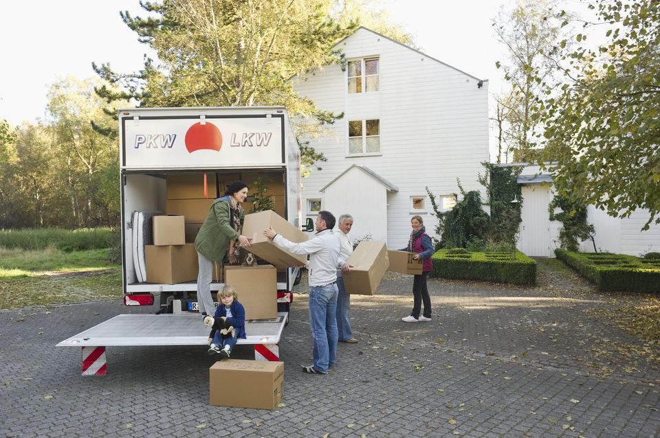 Family loading boxes into truck for moving house
