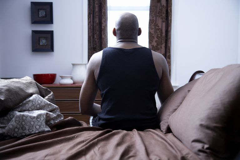 Mature man sitting on bed, rear view