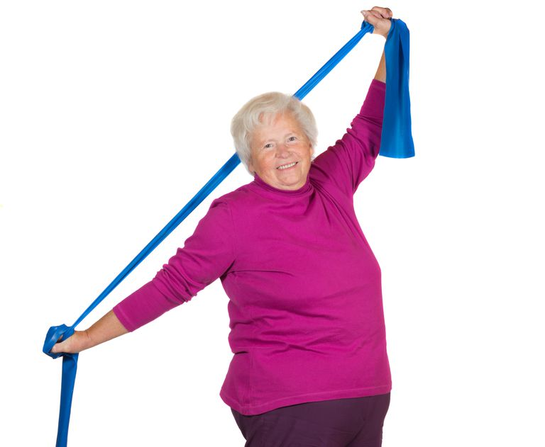 A senior woman exercises her back using a resistance band.