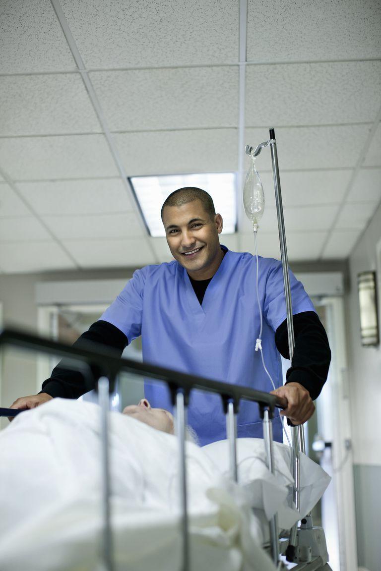Male nurse pushing gurney looking at camera