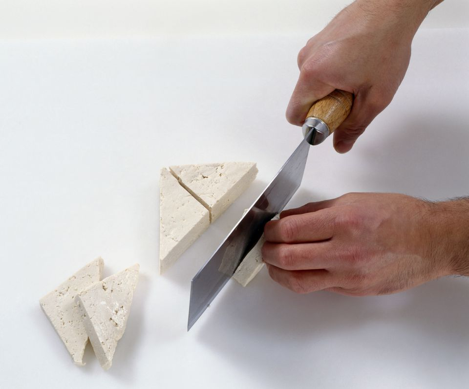 Cutting tofu into triangle shapes, using a cleaver