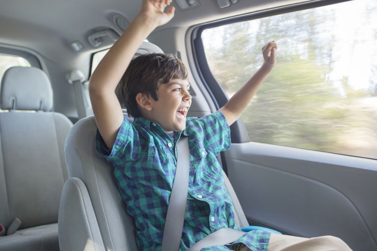 Enthusiastic boy cheering in back seat of car