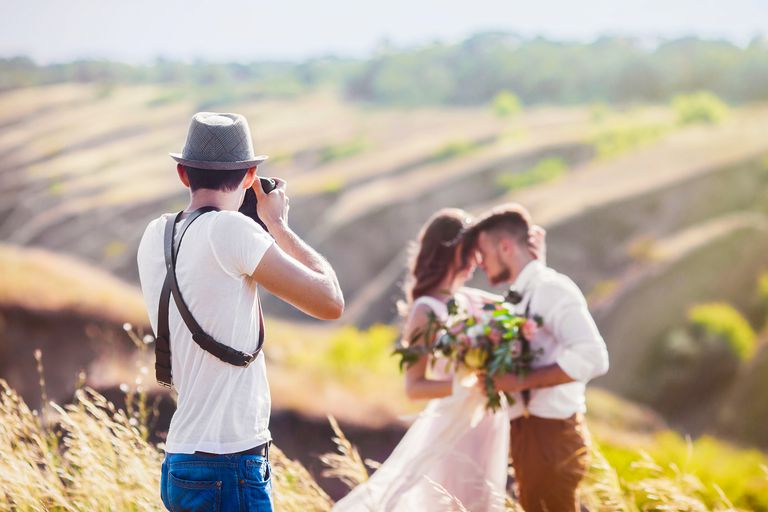 Freelance photographer photographing bride and groom