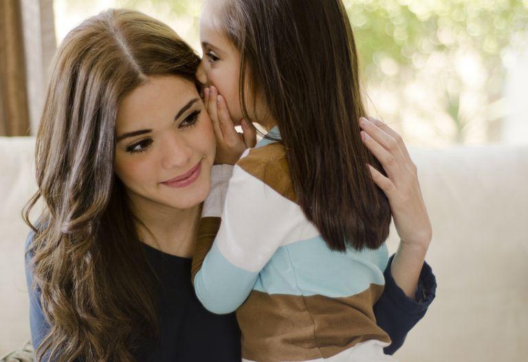 child tattling - girl whispering in her mom's ear