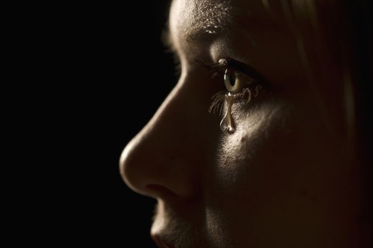 Studio portrait of a young Caucasian woman crying (close-up)