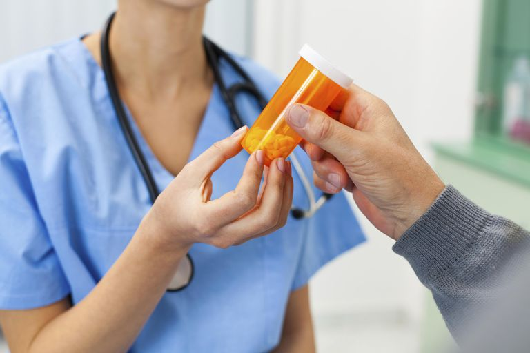 Nurse giving pills to a patient