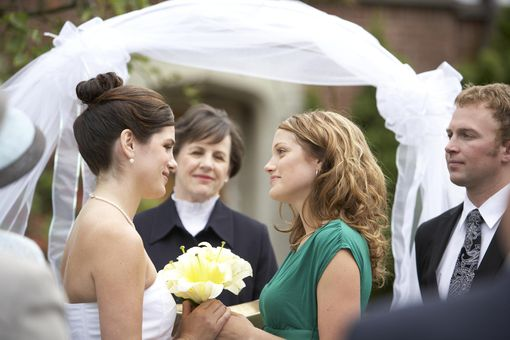 Lesbian couple smile at each other during wedding ceremony