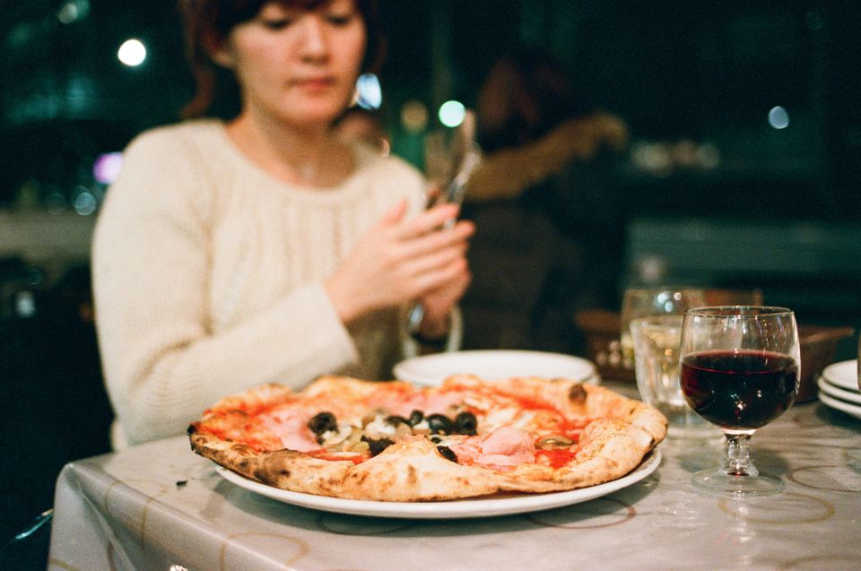Woman Eating Pizza With Wine At Restaurant