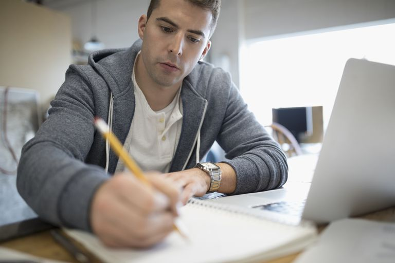 Focused creative businessman writing in notebook at laptop