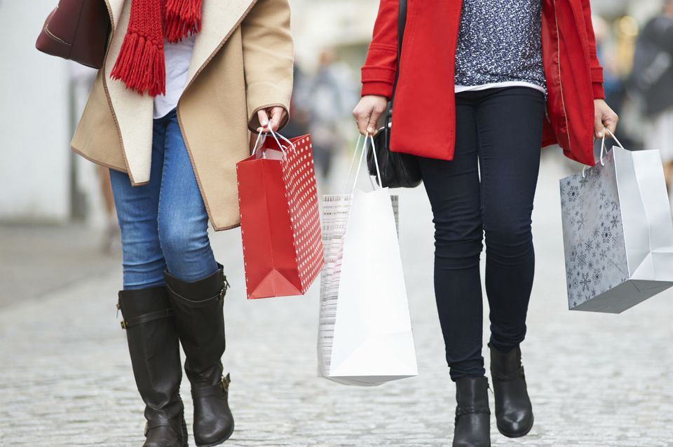 Friends carry Christmas shopping on a busy street.