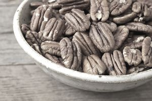 Bowl of pecan nuts on old wood table
