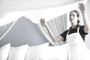 Maid in hotel room making bed