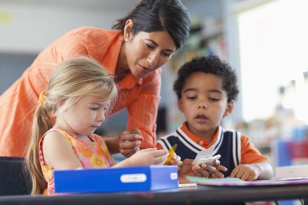 Teacher bending to help student in classroom