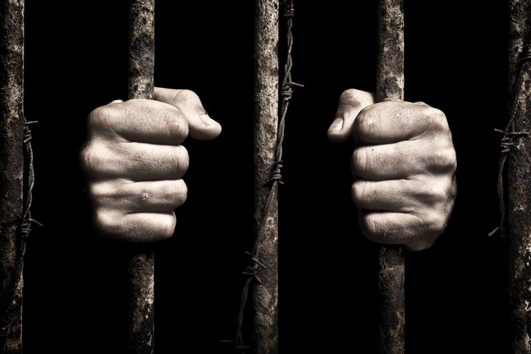 Long time-Two hands holding jail bars