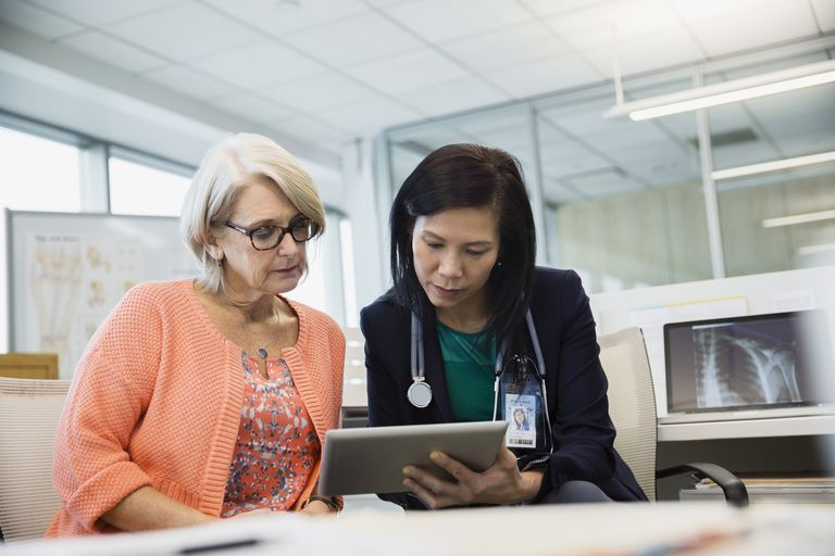 Doctor and patient using digital tablet in clinic