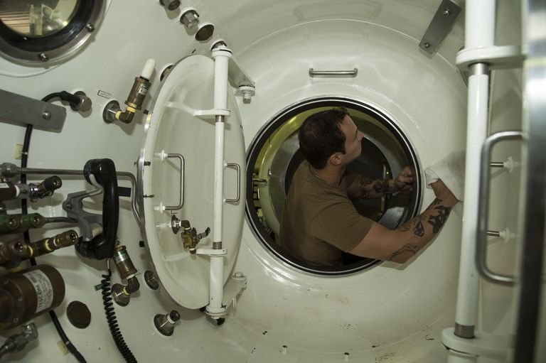 Navy Diver 2nd Class Josh King, assigned to Commander, Task Group (CTG) 56.1, cleans the inside of a transportable recompression chamber system (TRCS) as part of regular maintenance. The TRCS simulates surface decompression for the treatment of decompression sickness and pressure tests for prospective divers.