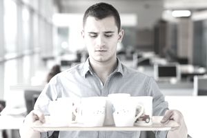 Man holding tray of coffee mugs