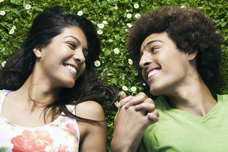 Teenage couple laying in grass holding hands