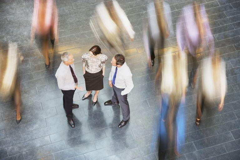 People rushing past business people talking