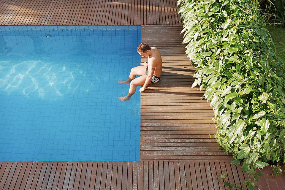 Young Man Sitting By Swimming Pool Dangling Legs In Water