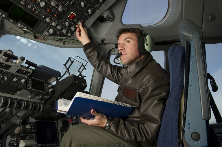 A U.S. Air Force pilot conducts his preflight checklist during engine start up on the flight deck.