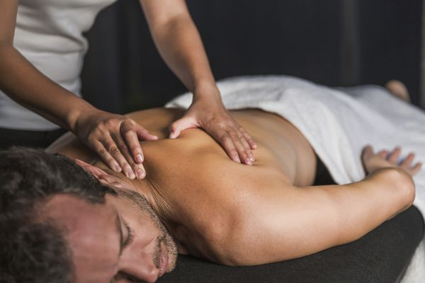 Man receives back massage in spa
