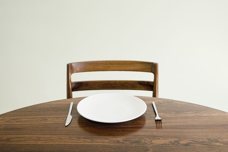 Empty plate with knife and fork on table.