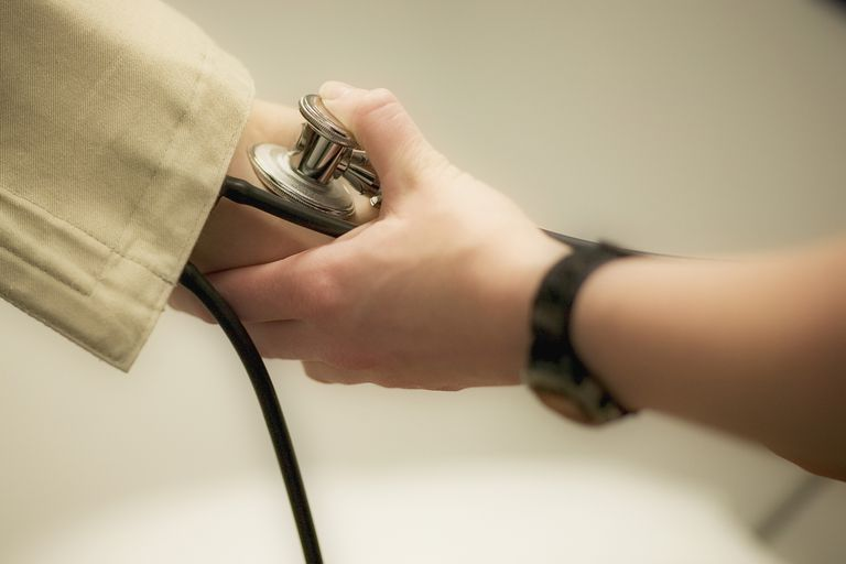 Checking a patient's blood pressure.