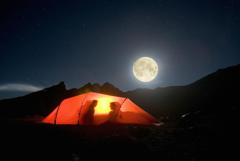 Couple in tent on mountain under full moon