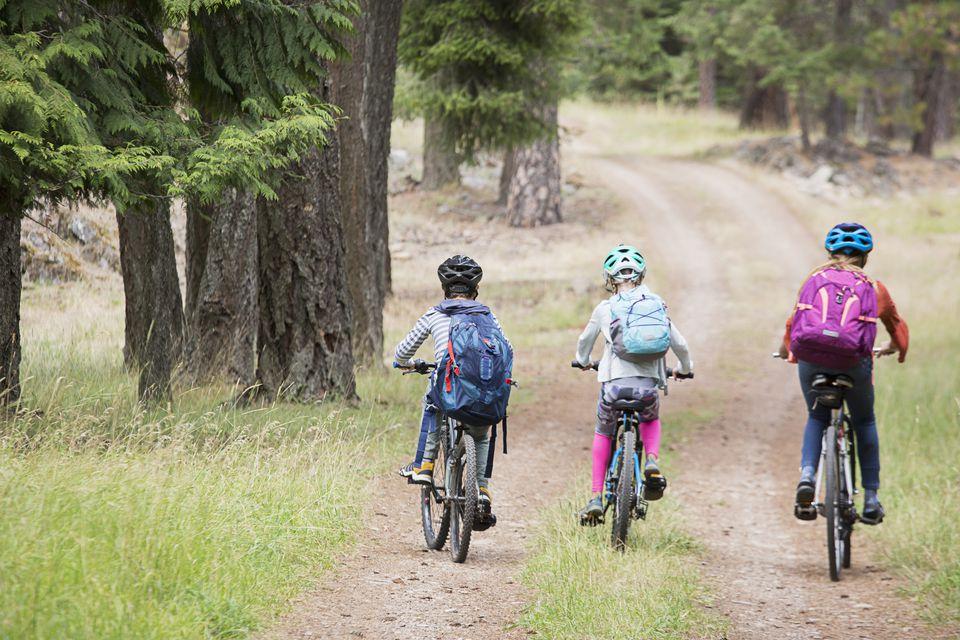 Caucasian boy and girls riding bikes on path