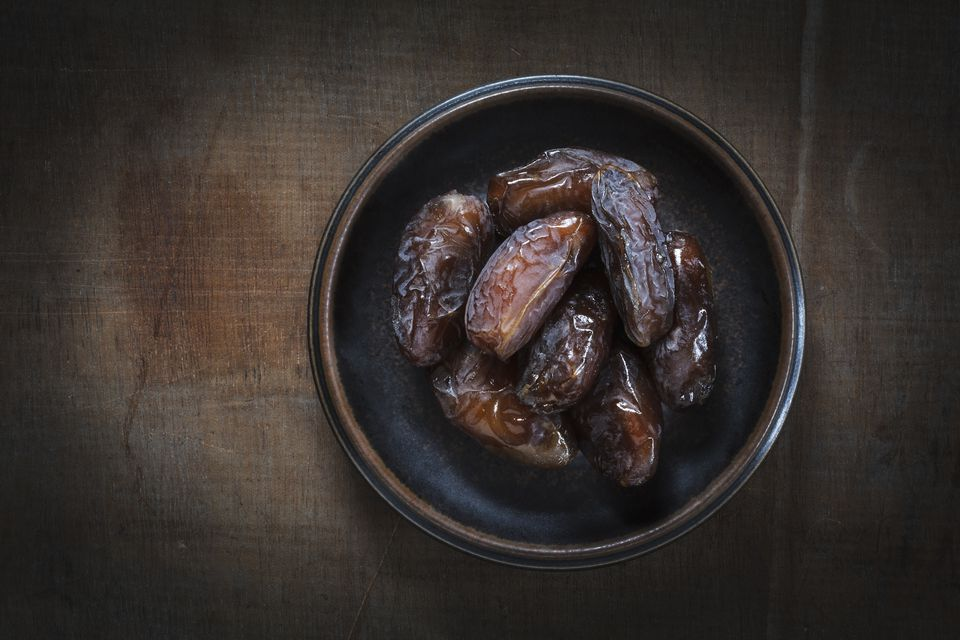 Bowl of Medjooll dates on wood