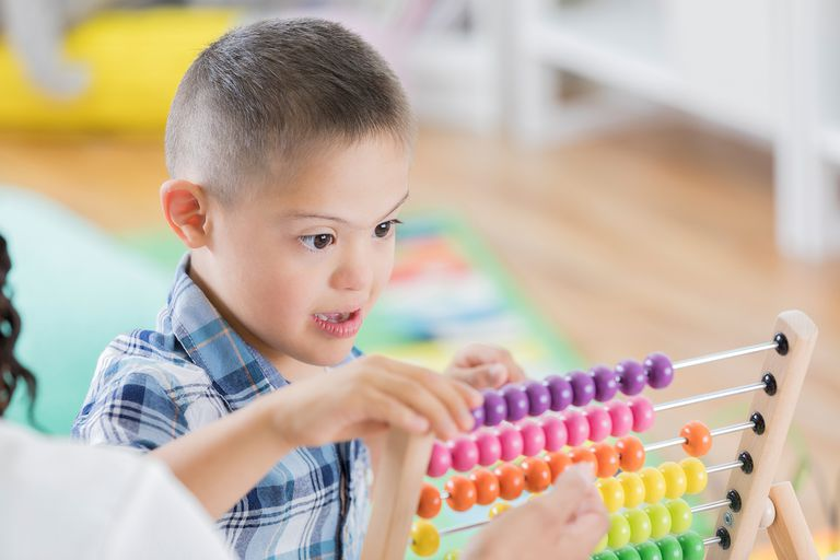 Boy with Down Syndrome uses abacus at school