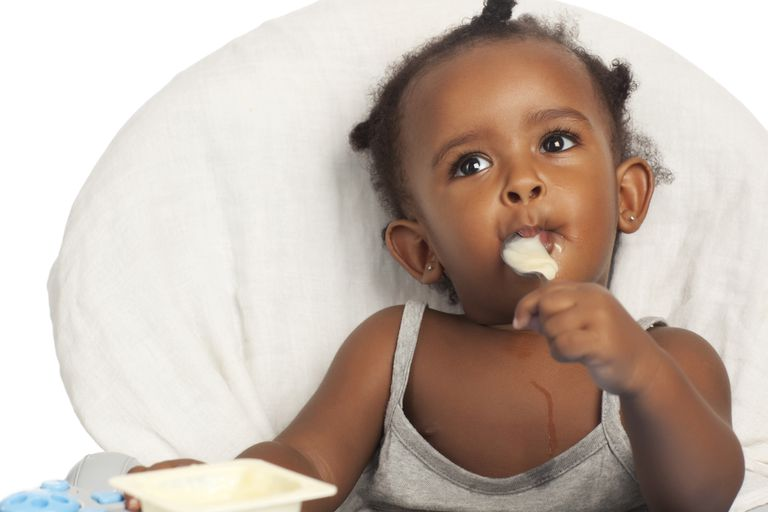 A baby feeding herself yogurt.