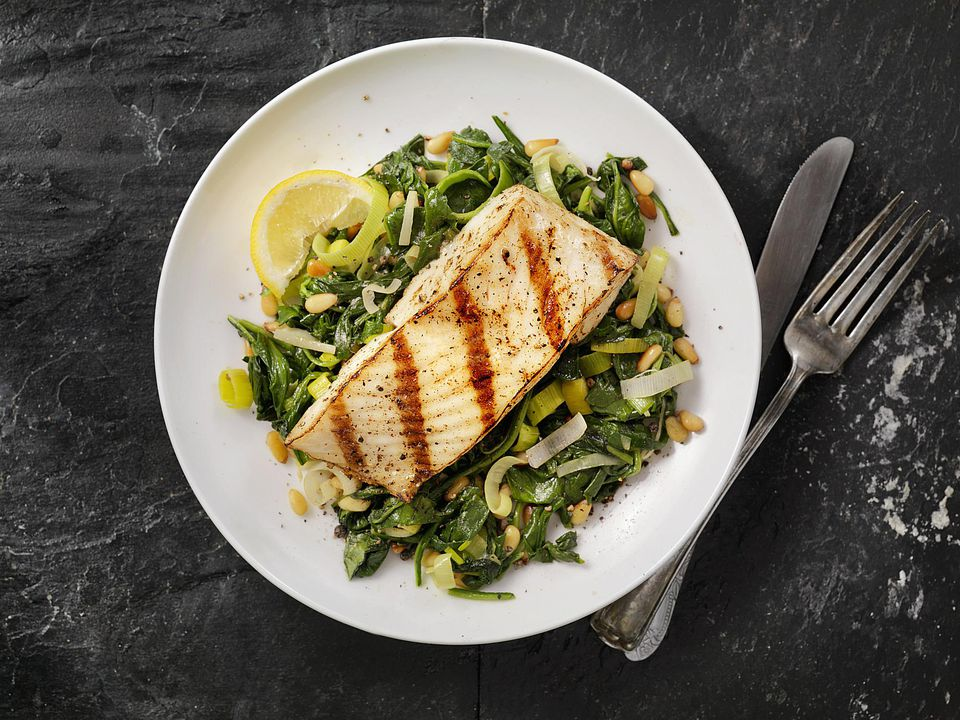 A plate of grilled halibut and vegetables