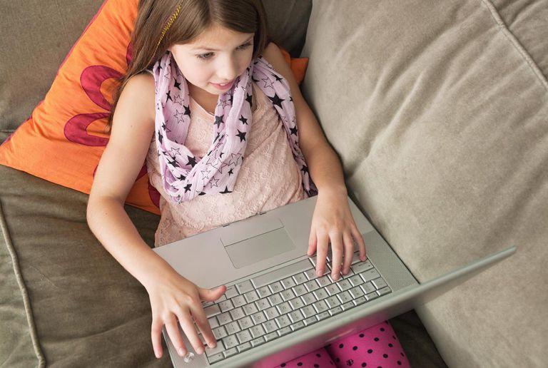 Girl using laptop on sofa