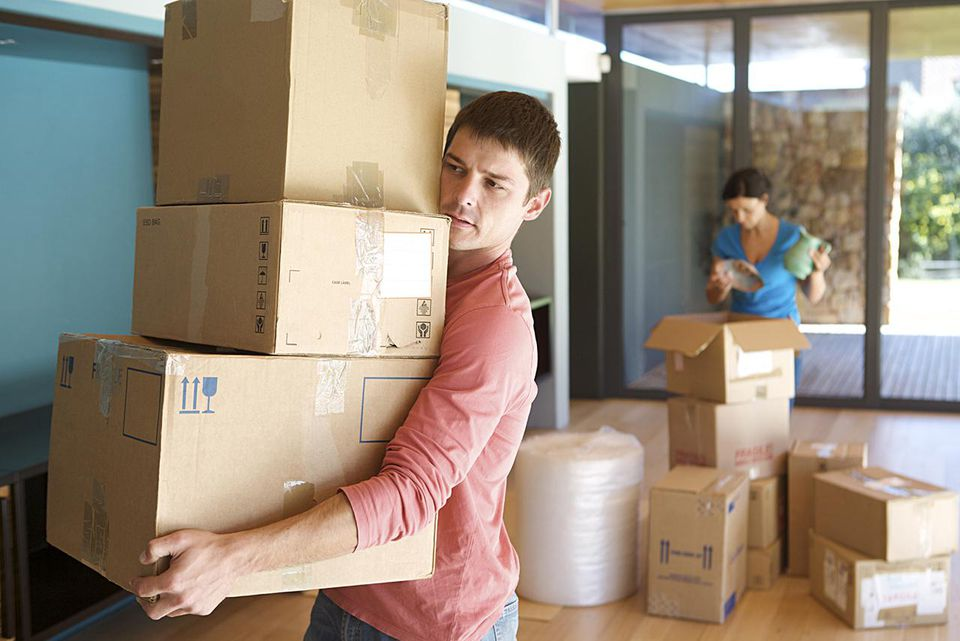 Mature man, aged 31, carrying boxes out of a packed up room while moving house