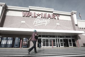 Picture of a woman walking in front of a Walmart store